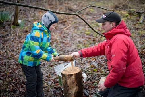 Dad kneeling across from child - splitting kindling with a knife and a mallet